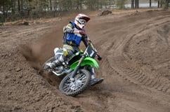 一辆摩托车的MX竟赛者在逆转含沙轨道 免版税库存图片