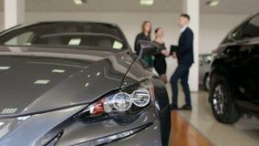 一辆新的汽车的特写镜头在陈列室里,背景人民的选择汽车 影视素材