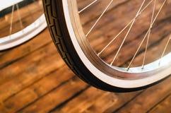 一辆时髦的自行车和在时髦的木背景的一个棕色橡胶轮胎的轮子有一个白色外缘的 免版税库存图片