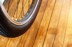 一辆时髦的自行车和在时髦的木背景的一个黑橡胶轮胎的轮子有一个黑外缘的 免版税库存图片