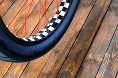 一辆时髦的自行车和在时髦的木背景的一个黑橡胶轮胎的轮子有一个黑白外缘的 库存照片