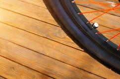 一辆时髦的自行车的轮子有一个黑外缘和一个黑橡胶轮胎的,红色轮幅,时髦的木背景 免版税库存照片