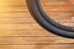 一辆时髦的自行车的轮子有一个黑外缘和一个黑橡胶轮胎的,红色轮幅,时髦的木背景 库存照片