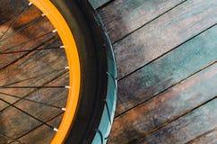 一辆时髦的自行车的轮子有橙色外缘和橡胶轮胎盖子的,木背景 库存照片