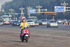 一辆时兴的e自行车的中国女孩在市中心,北京,中国 库存图片