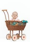 一辆柳条摇篮车的新女婴 免版税库存照片