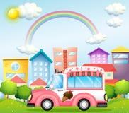 一辆桃红色冰淇凌公共汽车在城市 库存图片