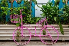一辆桃红色自行车的金属小雕象在其中一条的城市的街道 免版税库存照片
