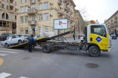 一辆残破的汽车VAZ-2107的撤离在城市街道上的 免版税库存照片
