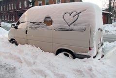 一辆汽车到雪里,与箭头图片的心脏在窗口 库存照片