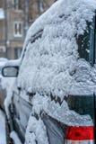 一辆汽车在用在飞雪的雪报道的停车场的冬天 免版税库存图片