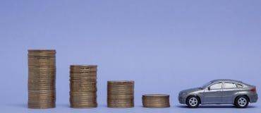 一辆汽车的一个灰色模型有硬币的以在紫色背景的一张直方图的形式 借贷,储款,保险的概念 免版税库存图片