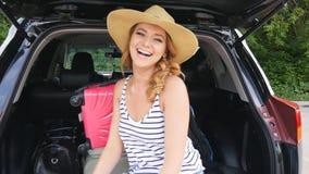 一辆汽车的后车箱的女孩带着手提箱的 影视素材