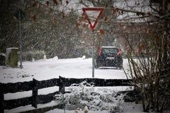 一辆汽车的图象在与雪和交通标志的冬天 免版税库存图片