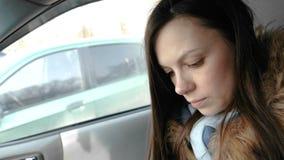 一辆汽车的妇女有一个手机的 看某事在手机的年轻美丽的深色的妇女 股票录像