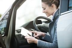 一辆汽车的微笑的妇女有片剂的 免版税库存照片