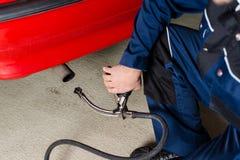 一辆汽车的技工测量的尾气在车库的 库存照片