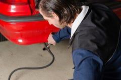 一辆汽车的技工测量的尾气在车库的 免版税库存照片