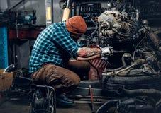 一辆汽车的有胡子的男性修理的引擎在车库的 库存图片