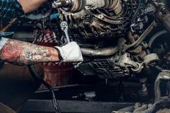 一辆汽车的有胡子的男性修理的引擎在车库的 图库摄影