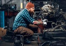 一辆汽车的有胡子的男性修理的引擎在车库的 库存照片