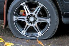 一辆汽车的泄了气的轮胎在路面的 库存图片