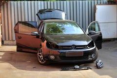 一辆汽车的自已修理在夏天,在车库附近 改变的车灯 没有幅射器前面车灯和格栅的黑hatcback  免版税库存图片