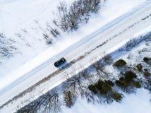 一辆汽车的鸟瞰图在冬天路的 冬天风景乡下 多雪的森林航拍有一辆汽车的在路 图库摄影