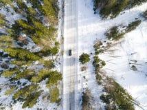 一辆汽车的鸟瞰图在冬天路的 冬天风景乡下 多雪的森林航拍有一辆汽车的在路 库存图片