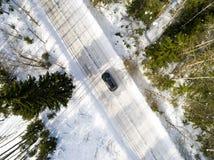 一辆汽车的鸟瞰图在冬天路的 冬天风景乡下 多雪的森林航拍有一辆汽车的在路 免版税图库摄影