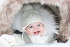 一辆温暖的婴儿推车的愉快的笑的女婴 图库摄影