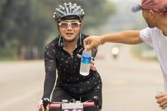 一辆漫长的路自行车的女孩疲倦到达目的地 免版税库存图片