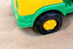 一辆玩具汽车的轮子在沙子的 免版税库存图片