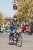 一辆生锈的老自行车的男性前辈,上海,中国 免版税图库摄影