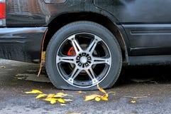 一辆生锈的老黑暗的汽车的泄了气的轮胎 免版税库存图片