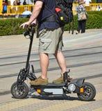 一辆电滑行车的人在城市街道上 免版税图库摄影