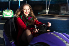一辆电碰撞用汽车的十几岁的女孩 免版税图库摄影