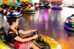 一辆电碰撞用汽车的美丽的女孩在游乐园 免版税库存照片