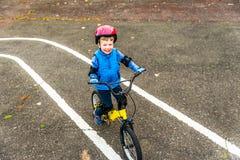 一辆男孩骑马自行车的顶上的看法有户外安全帽的在秋天公园 库存照片