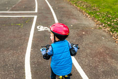 一辆男孩骑马自行车的顶上的看法有户外安全帽的在秋天公园 图库摄影
