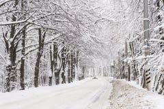 一辆白色汽车沿用雪盖的路乘坐 免版税库存照片