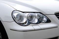 一辆白色汽车的大聚光灯。 库存照片