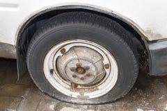 一辆白色汽车的老平的轮子有一个生锈的轮胎的 关闭老fl 免版税图库摄影