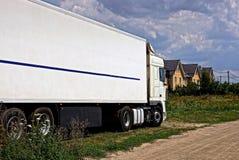 一辆白色长的卡车在草站立在一条含沙农村路附近 库存照片