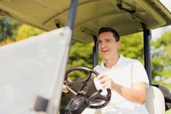 一辆白色高尔夫车的微笑的人今后热心地乘坐 免版税库存图片