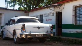 一辆白色经典汽车停放了房子前面  免版税库存照片