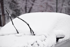 一辆积雪的汽车的风档刮水器 免版税图库摄影
