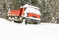 一辆红色卡车在冬天离开在森林附近 图库摄影
