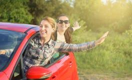 一辆红色汽车的女孩 库存图片