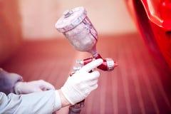 绘一辆红色汽车的工作者在绘画摊使用喷枪 免版税库存照片